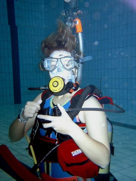 Eine Frau gibt Handzeichen unter Wasser