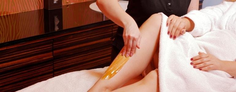 Body-Sugaring wird angewendet auf einem Bein