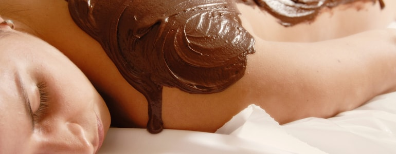 A chocolate mass is on a back of a woman